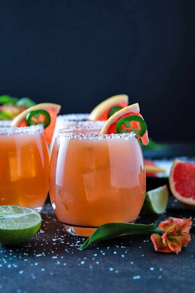 Front view of three grapefruit jalapeno margaritas garnished with jalapeno and grapefruit slices.