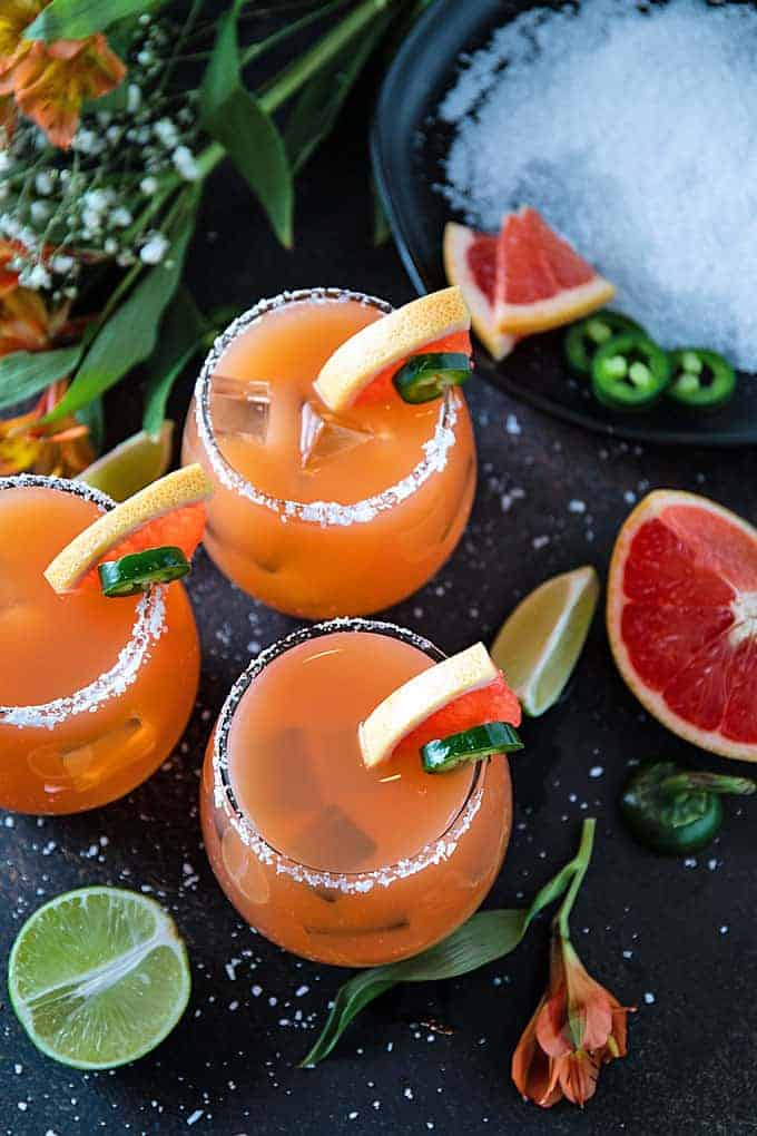Overhead shot of 3 grapefruit jalapeno margaritas on a dark background with lime and grapefruit wedges.