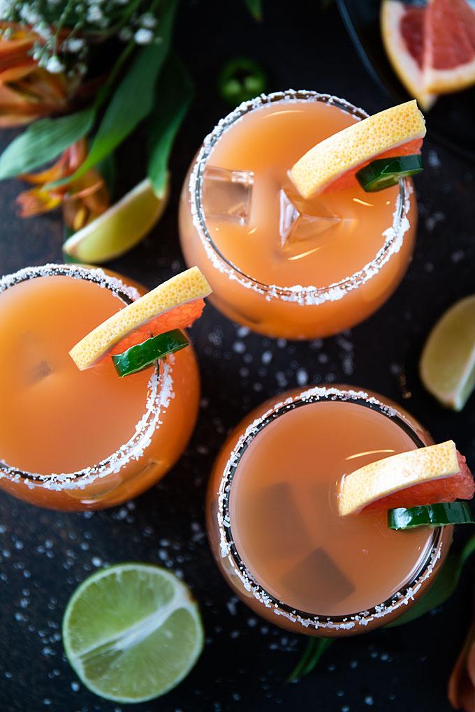Overhead shot of 3 grapefruit jalapeno margaritas in glasses rimmed with salt and garnished.
