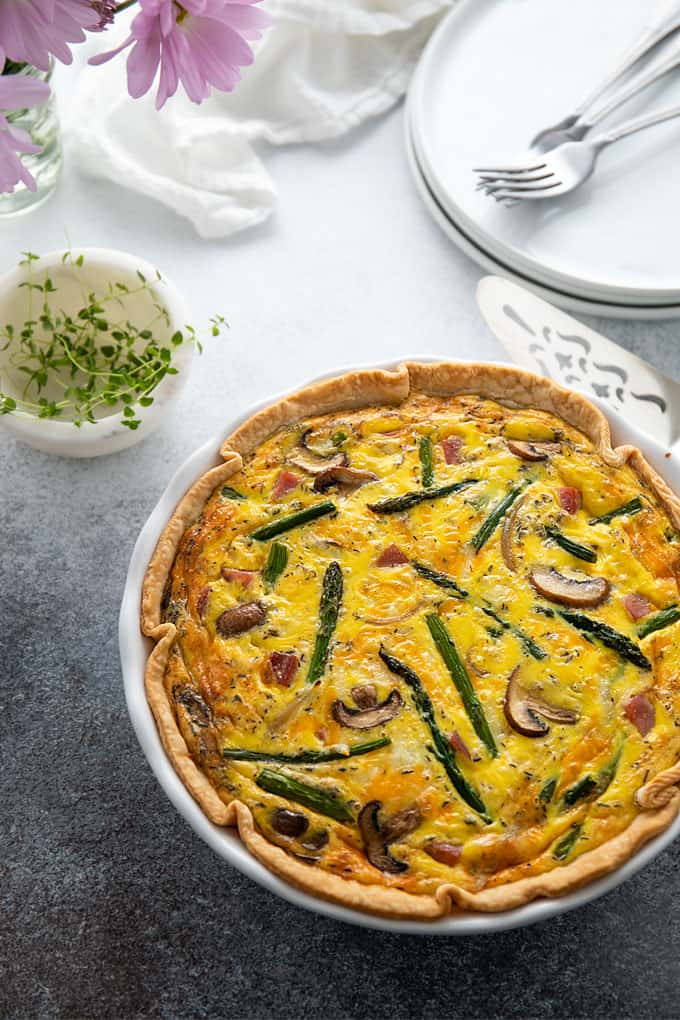 Overhead shot of a ham, asparagus and mushroom quiche beside a pie server and small bowl of fresh thyme sprigs.
