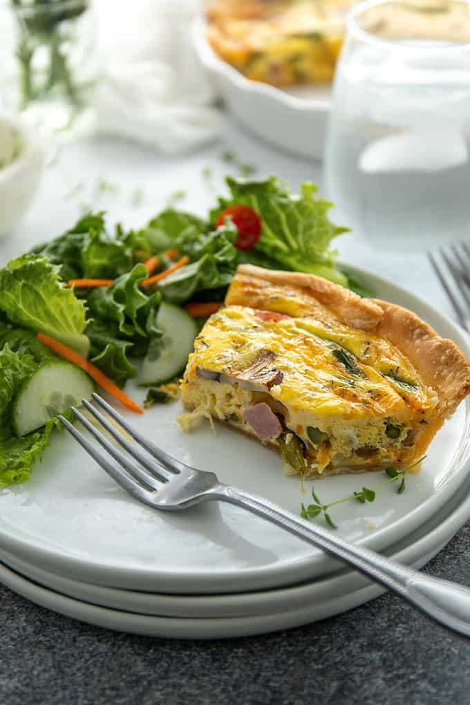 A slice of ham, mushroom and asparagus quiche on a round white plate with a garden side salad and a fork.