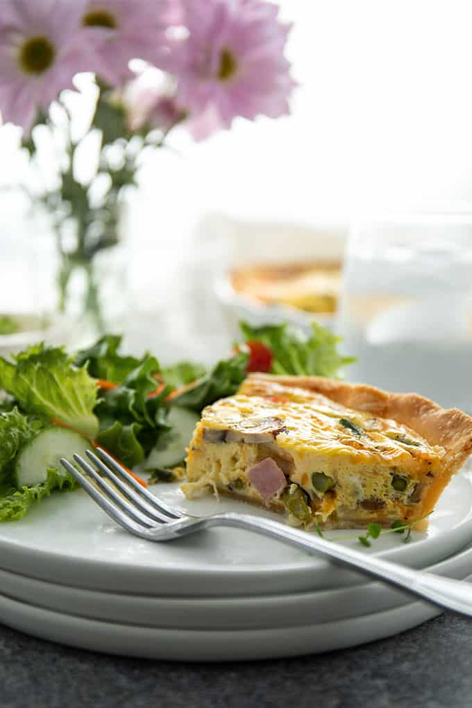 Front view of a cut slice of ham, mushroom and asparagus quiche on a white plate with a fork and salad.
