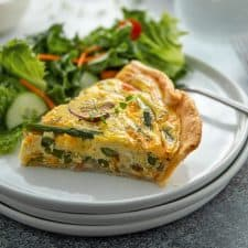 Front view of a slice of ham, asparagus and mushroom quiche on a round white plate with a garden salad.