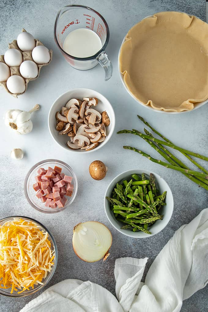 Overhead shot of ham, asparagus and mushroom quiche ingredients.