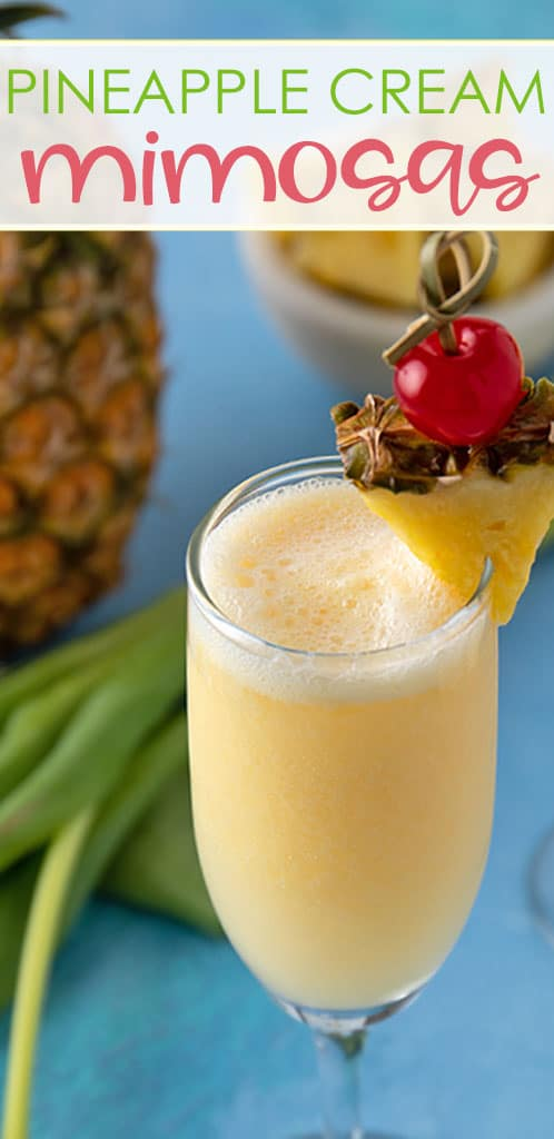 Closeup of a pineapple cream mimosa garnished with a fresh pineapple wedge and maraschino cherry.