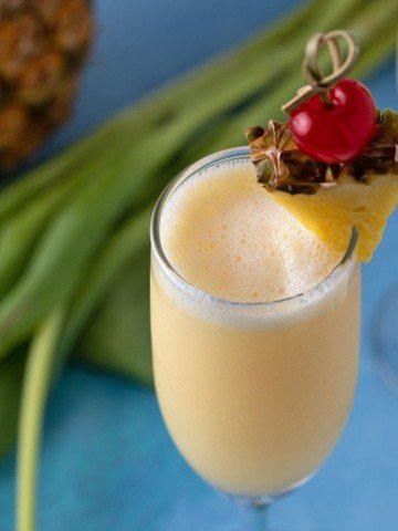 A pineapple cream mimosa in a champagne flute garnished with a pineapple wedge and cherry.