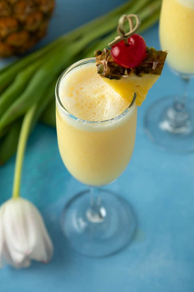 A pineapple cream mimosa garnished with a pineapple wedge and maraschino cherry beside a bunch of fresh tulips.