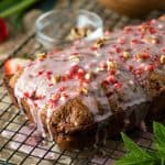 A loaf of glazed strawberry pecan bread on a black wire rack beside a sprig of fresh mint.