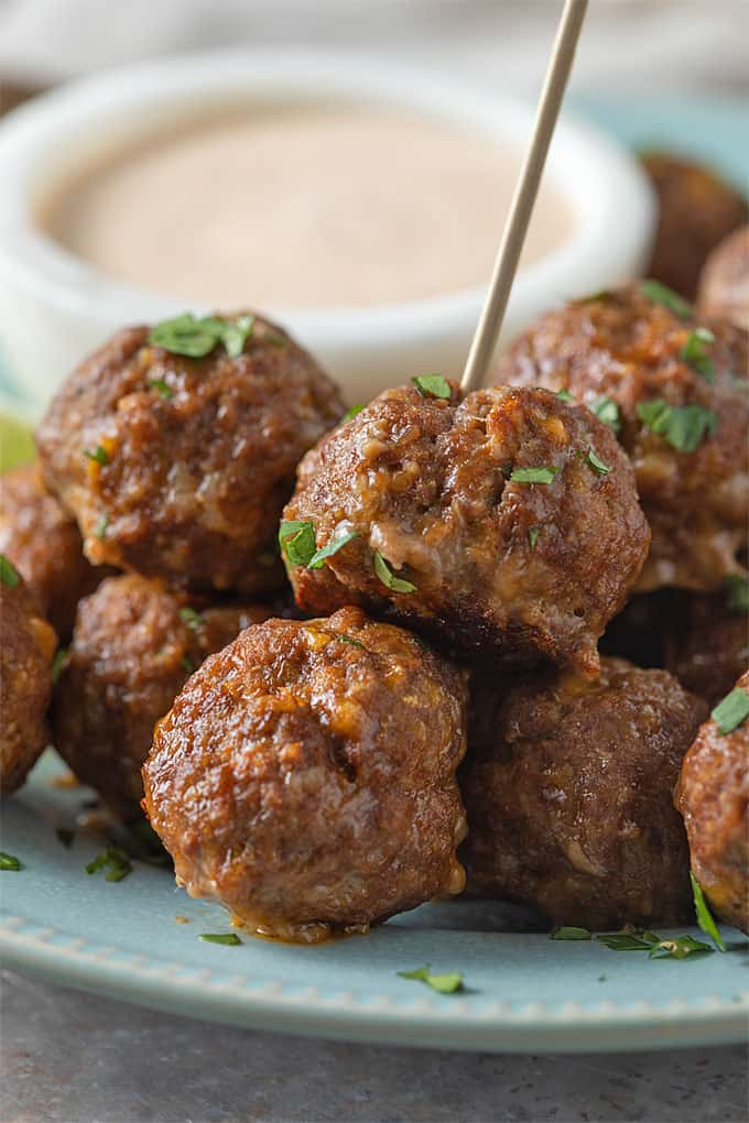 A closeup front view of taco ranch meatballs with taco ranch sauce in the background.