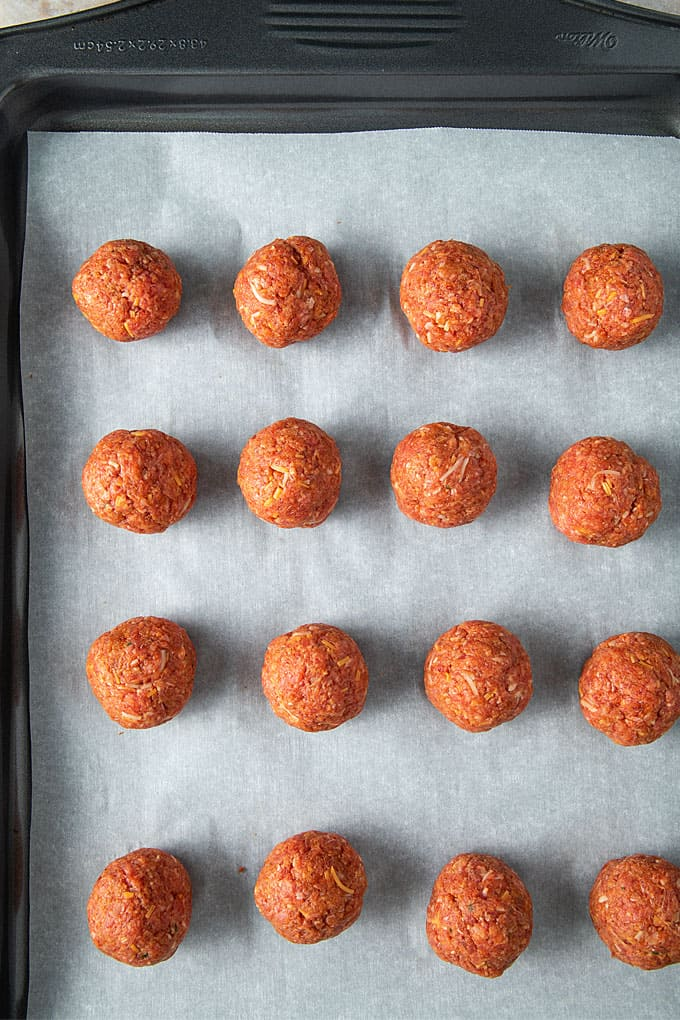 Overhead shot of unbaked taco ranch meatballs on a baking sheet lined with parchment paper.