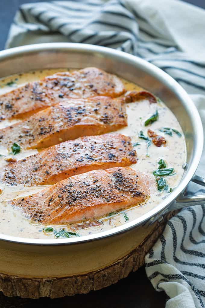 Front view of 4 salmon fillets in a creamy Tuscan sauce in a round stainless steel skillet