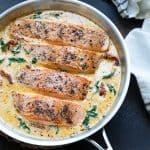 Overhead view of 4 salmon fillets in a tuscan cream sauce in a stainless steel skillet