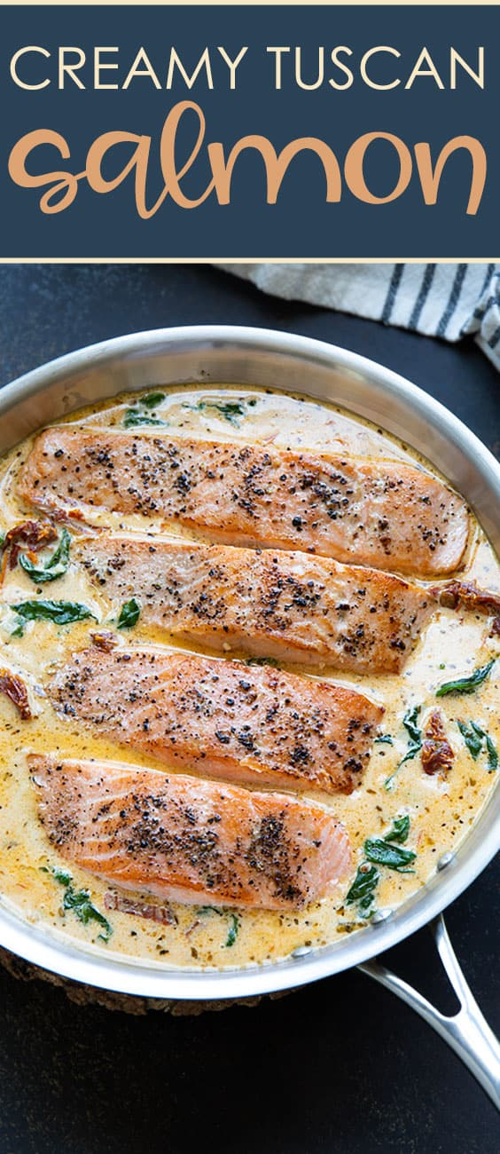 Four pieces of cooked salmon in a cream sauce in a skillet.