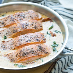 Four salmon fillets with cream sauce in a stainless skillet.