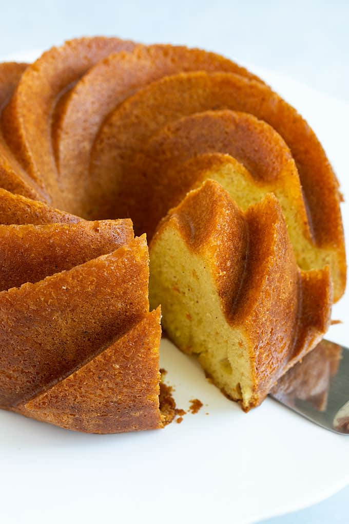 Spiced orange rum (bundt) cake on a round white serving platter that has been sliced with a serving knife.