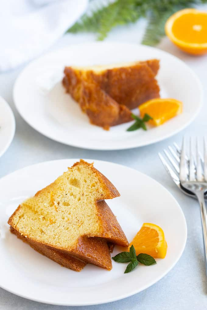 Front view of sliced spiced orange rum cake on 2 round white plates beside 3 forks.