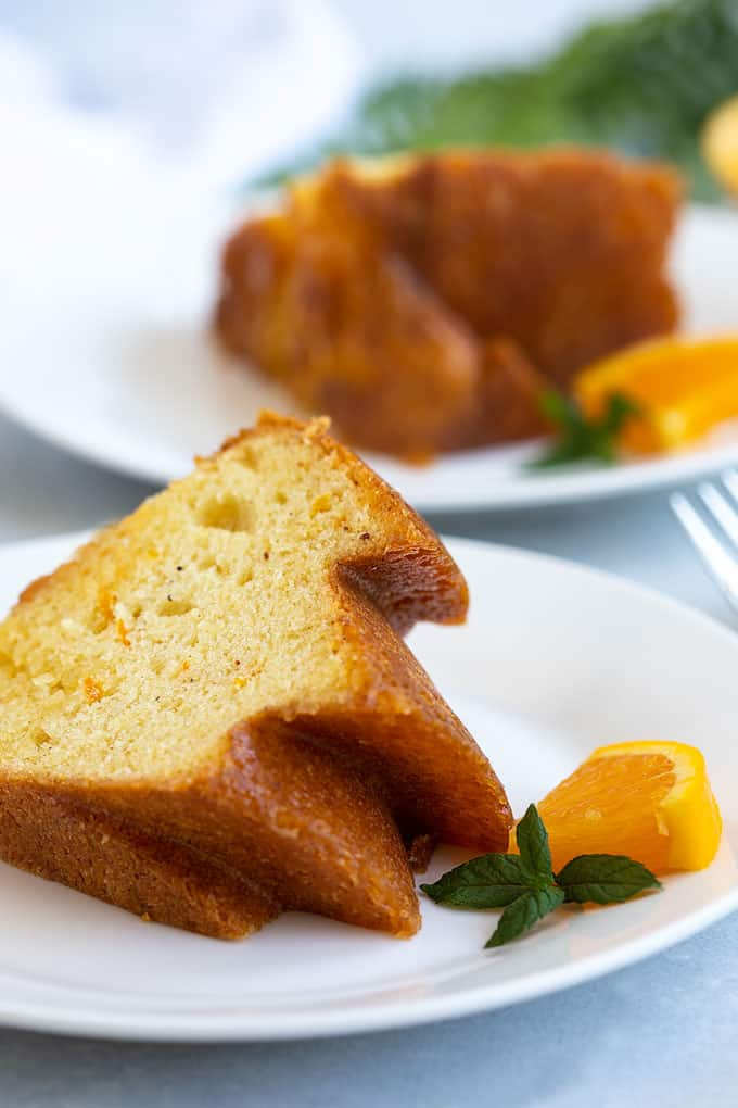 2 slices of spiced orange rum cake on 2 round plates garnished with an orange slice and mint sprig.