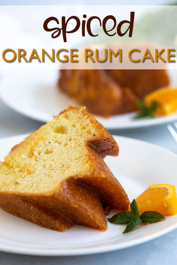 A slice of cake on a white plate beside a slice of fresh orange and mint.