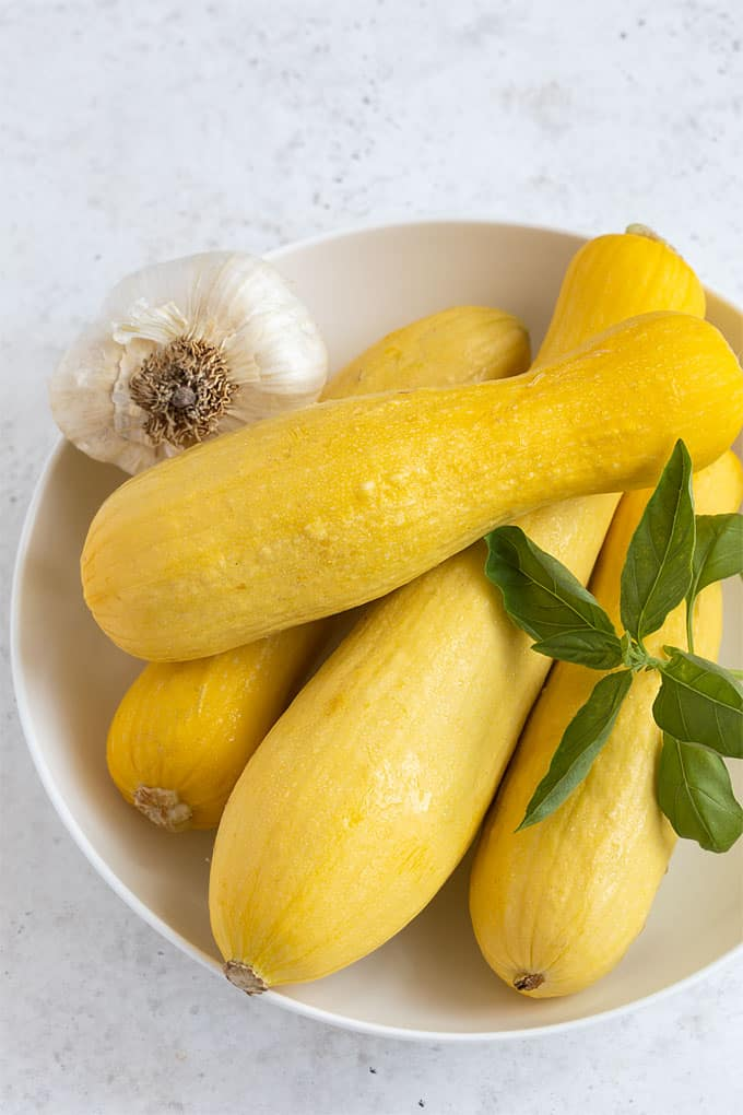 4 fresh yellow squash, a head or garlic and a sprig of fresh basil in a round white bowl.