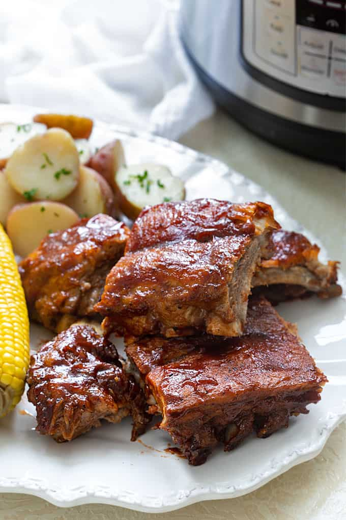Barbecue pressure cooker ribs on a platter with corn on the cob and potatoes with an Instant Pot in the background