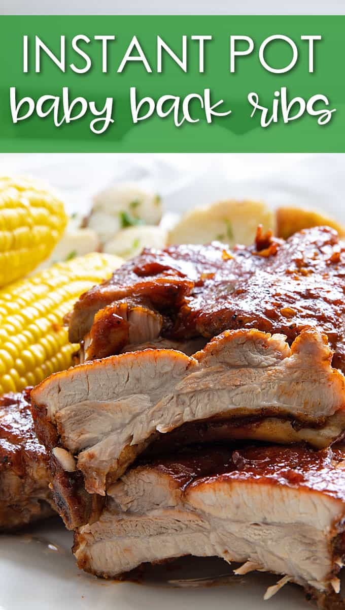 Front view of barbecue ribs on a plate with corn on the cob and potatoes.
