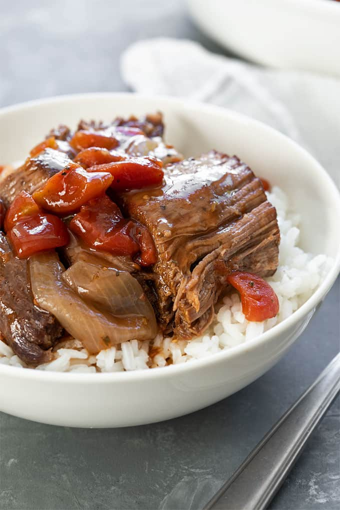 Closeup of Instant Pot Italian Pot Roast over rice in a white bowl