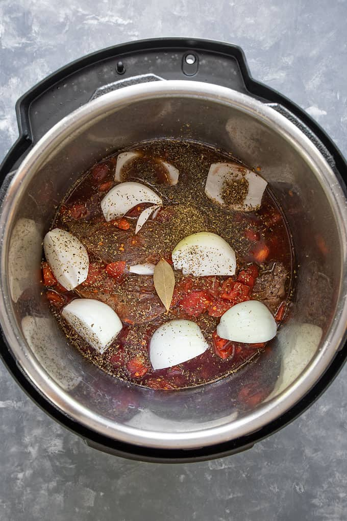 Beef chuck roast, canned tomatoes, onion wedges and seasonings in a pressure cooker before cooking