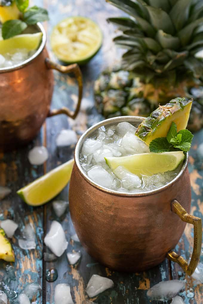 2 Moscow Mule cocktails in copper mugs garnished with fresh pineapple, lime wedges and mint sprigs