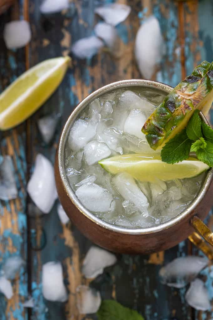 Overhead view of a pineapple mule cocktail in a copper mug garnished fresh pineapple, mint and lime