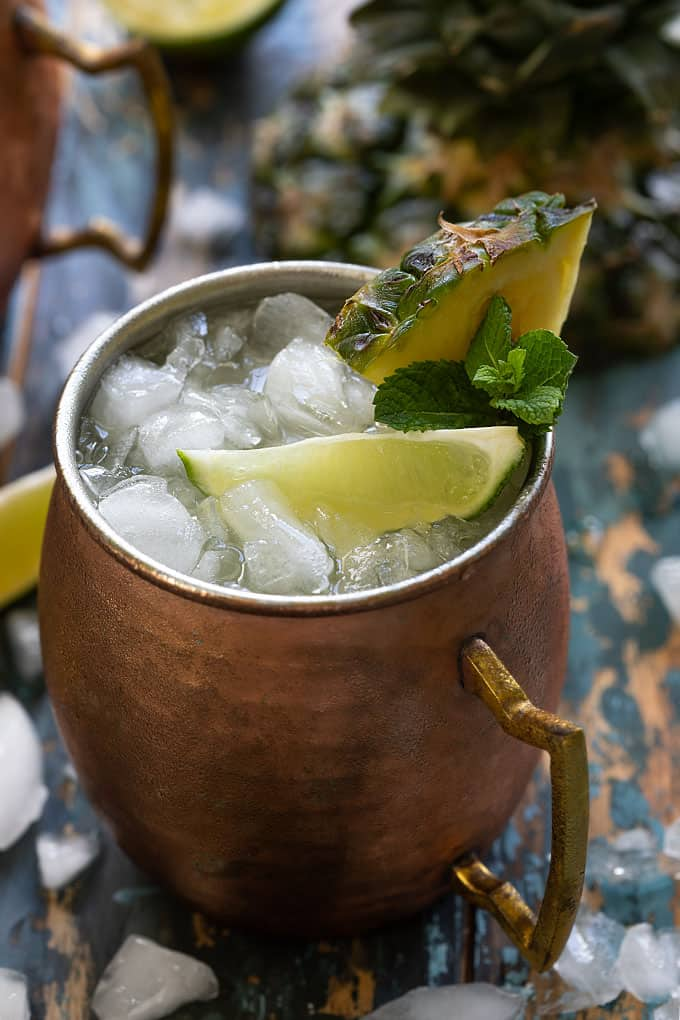 A closeup of a pineapple mule in a copper mug with crushed ice