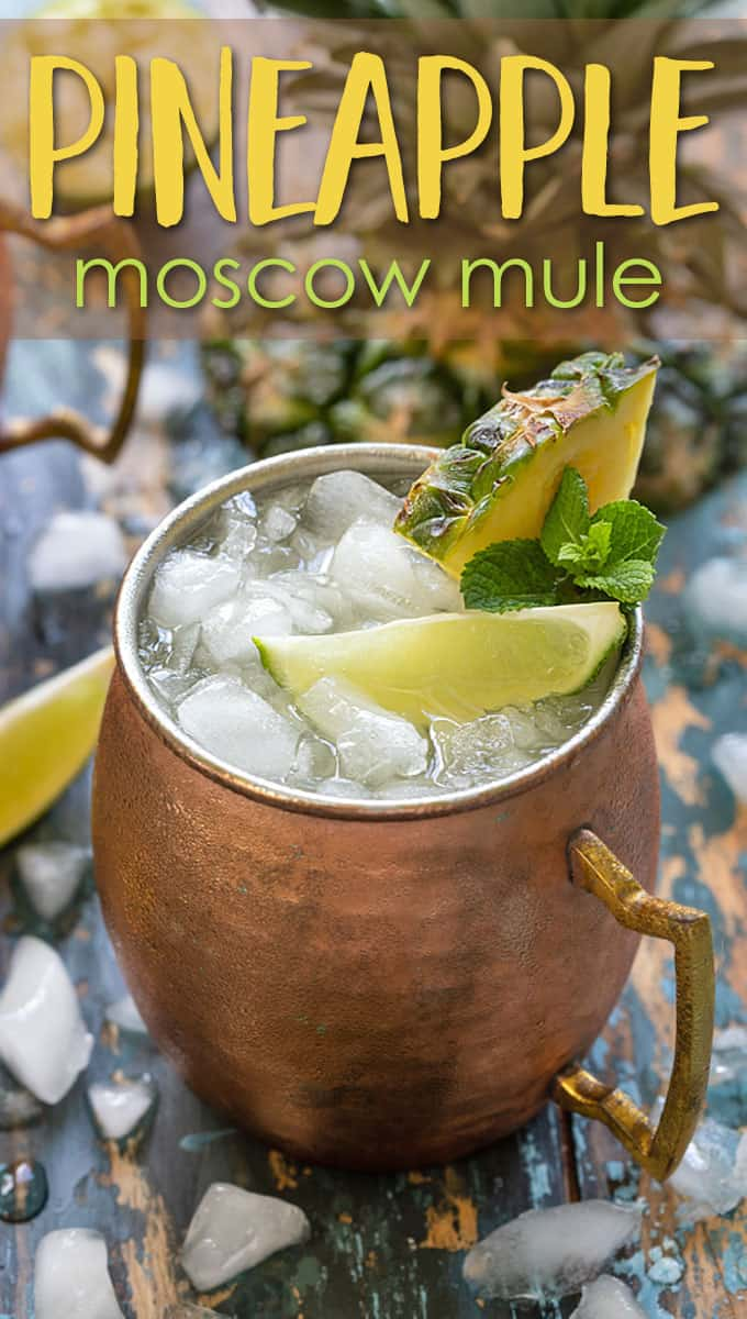 A mule cocktail in a copper mug garnished with fresh pineapple and lime.
