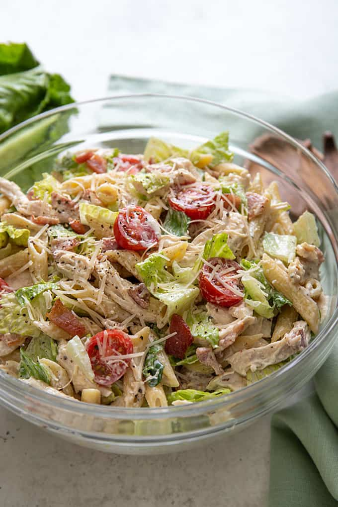 Closeup front view of chicken Caesar pasta salad in a glass bowl