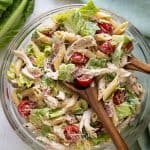 Overhead view of pasta salad with Caesar dressing, chicken, bacon and vegetables in a glass bowl with wooden serving utensils