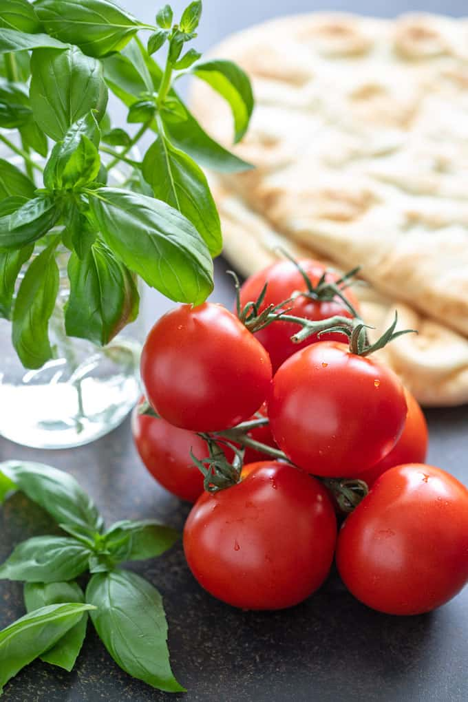 Fresh tomatoes, fresh basil in a glass with water and 2 slices of naan bread for margherita pizza