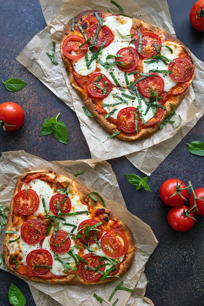 Overhead view of 2 margherita flatbread pizzas on parchment paper