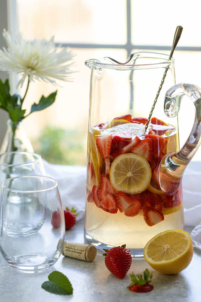 A glass pitcher of strawberry lemonade sangria beside 3 stemless wine glasses
