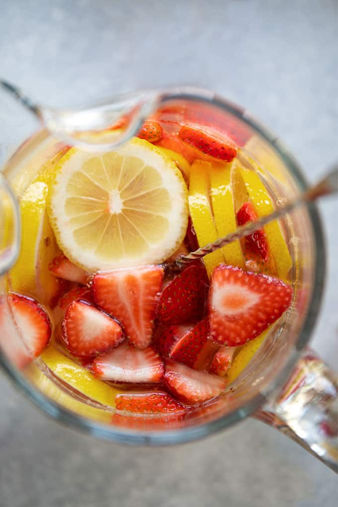 Overhead view of white wine sangria with fresh sliced strawberries and lemons in a glass pitcher with a stirrer
