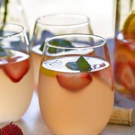 White wine sangria with strawberries and lemonade in 3 wine glasses beside a glass pitcher