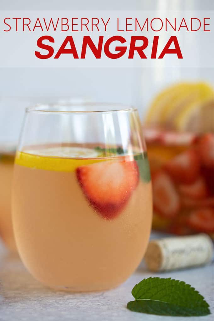 Front view of a glass of sangria with a fresh strawberry and lemon slice.