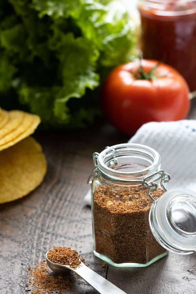 Taco seasoning in a spice jar with taco ingredients in the background