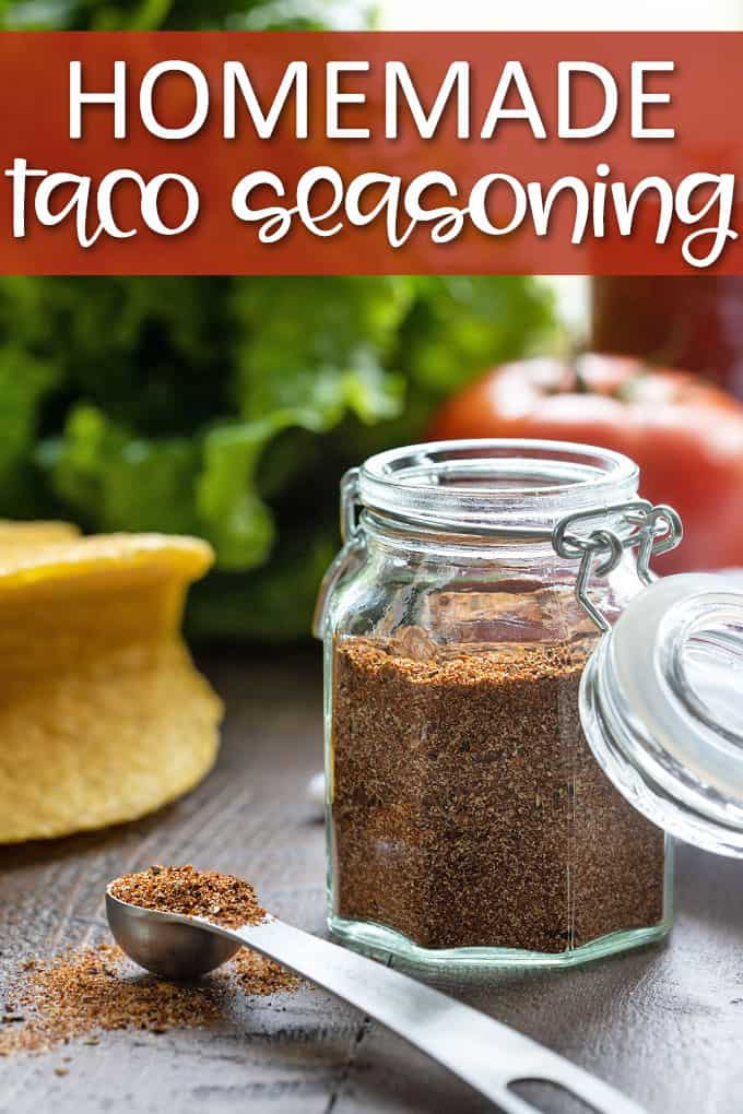Taco seasoning in a glass spice jar beside a measuring spoon with taco ingredients in background
