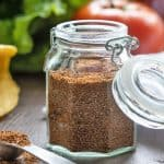 Taco seasoning in a glass spice jar beside a measuring teaspoon