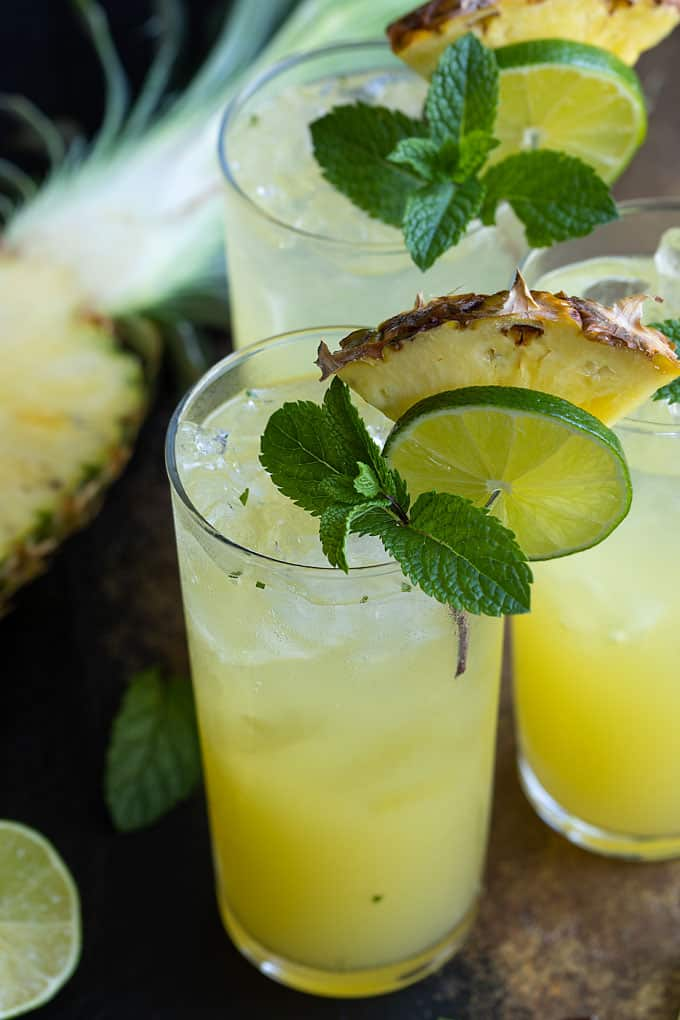 3 Pineapple Mojitos garnished with fresh pineapple, lime and mint