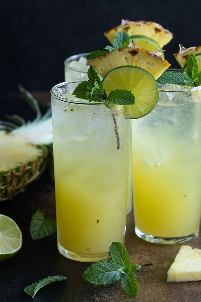 Front view of 3 pineapple mojitos with a fresh sliced pineapple in the background