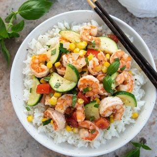 Overhead view of shrimp, corn and zucchini stir-fry over rice in a bowl with chopsticks