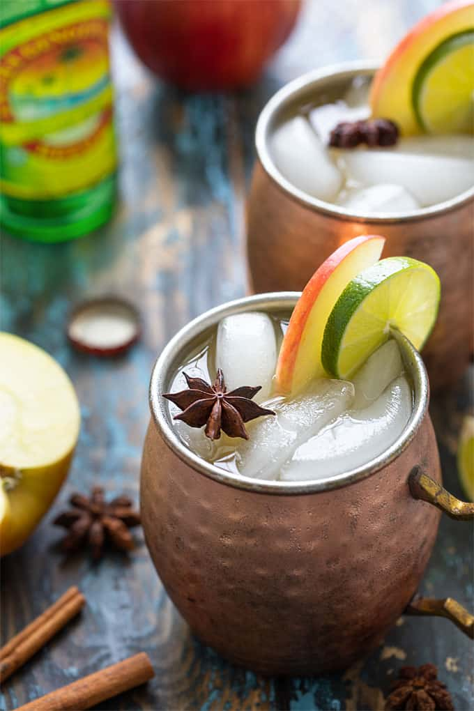 Two Apple Cider Mules garnished with apple, lime and a star anise