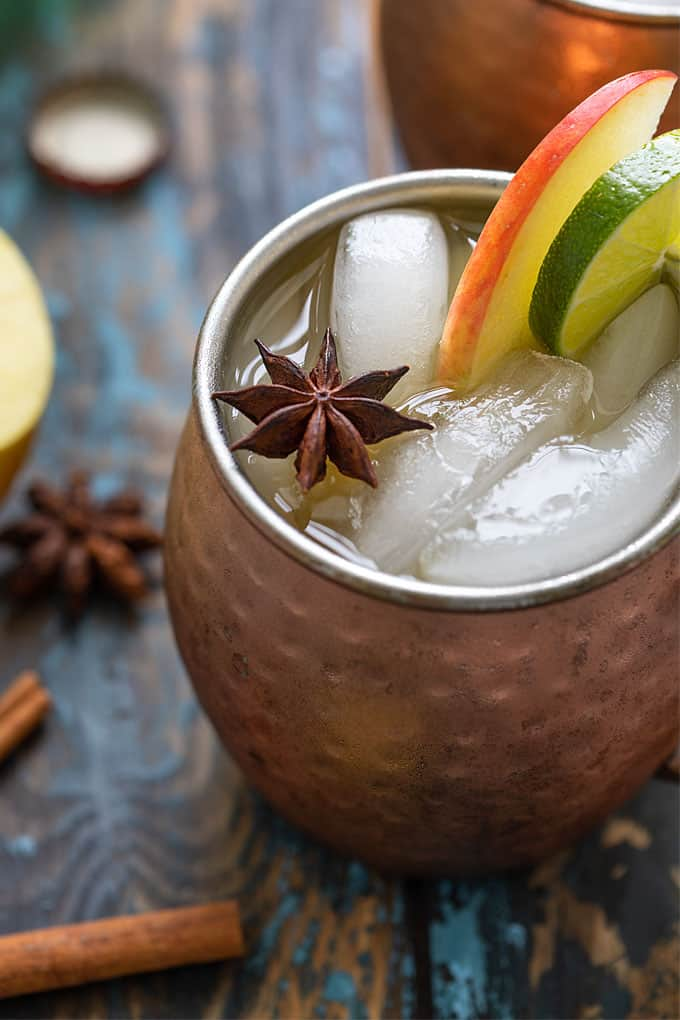 Closeup view of a garnished mule cocktail in a copper mug with ice.