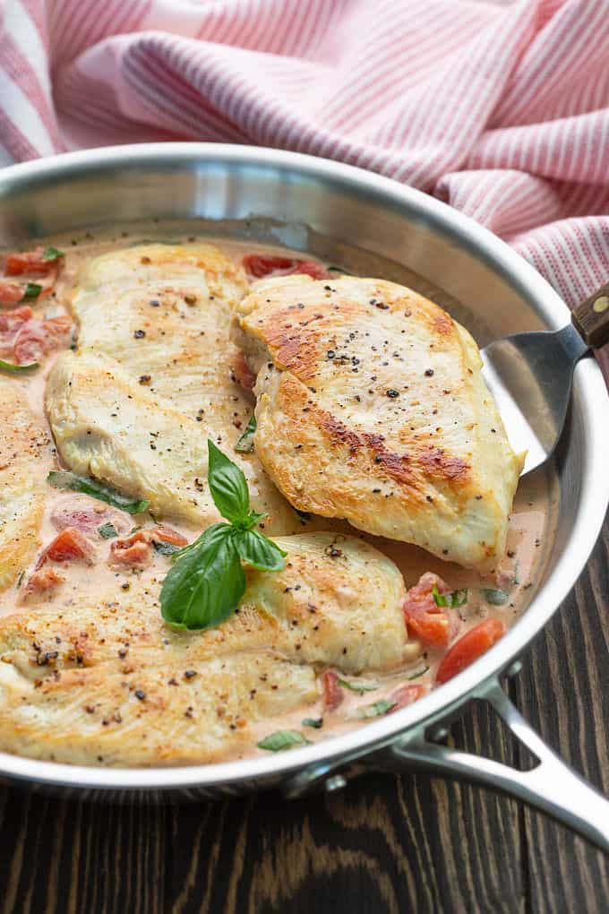 Chicken breasts in tomato basil cream sauce in a skillet with a spatula