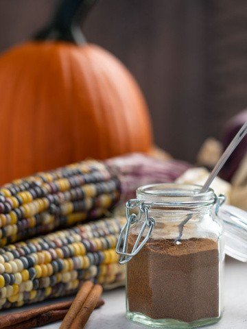 DIY pumpkin pie spice in a spice jar with a measuring spoon in the jar