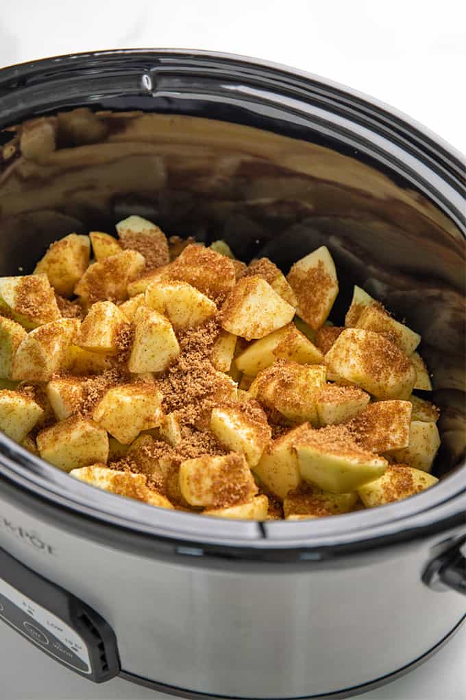 Peeled and chopped apples topped with brown sugar and apple pie spice in a slow cooker